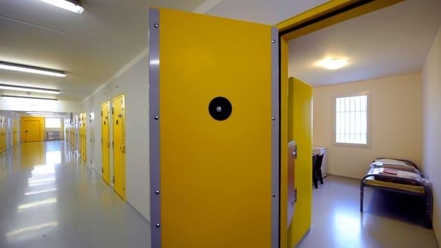 Blick in eine Gefängniszelle – die Zellentür steht offen.