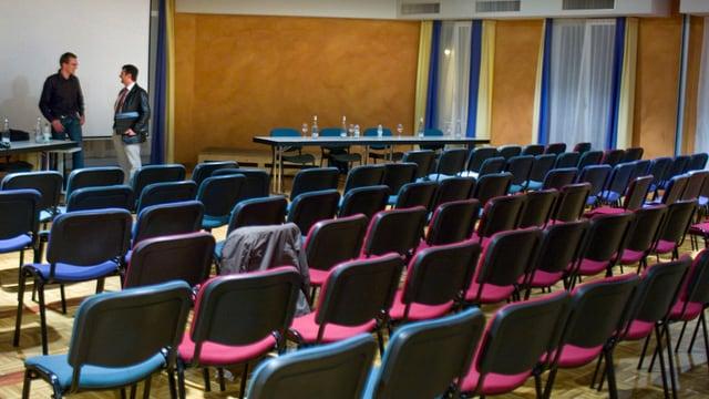 Leere Stühle in einem vollen Saal