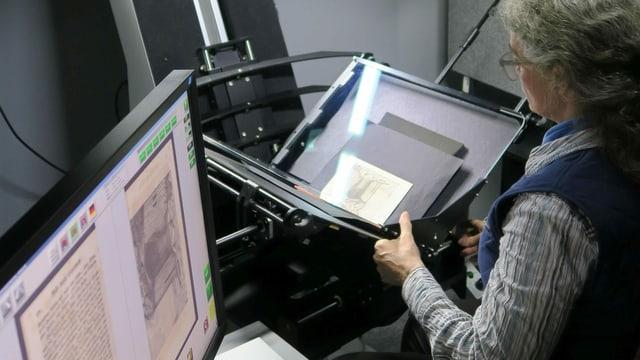 Eine Frau scannt ein altes Dokument ein.