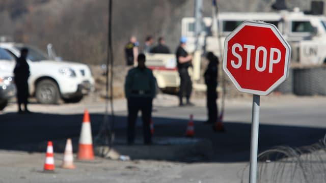 Unmik-Soldaten, Stoppschild, Stacheldraht und Verkehrshütchen an der Grenze zwischen Kosovo und Serbien.