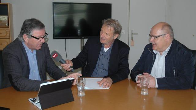 Der Walliserkorrespondent Reinhard Eyer sitzt in der Mitte und hält das Mikrofon dem Klub-Präsidenten Viktor Borter hin.