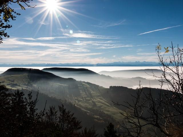 Vom Cellenchöpfli in Baselland ein Blick zu den  Alpen. Im Vordergrund zeigen sich am Hauberg Dunst- und Nebelschleier, darüber ist der Himmel mit ein paar dünnen Wolken bedeckt, die Sonne scheint.