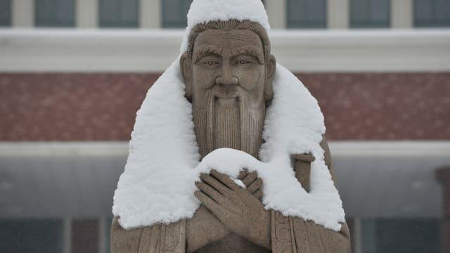Eine schneebedeckte Statue von Konfuzius.