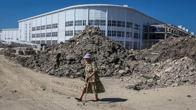 Eine Dame läuft bei einer Baustelle vorbei