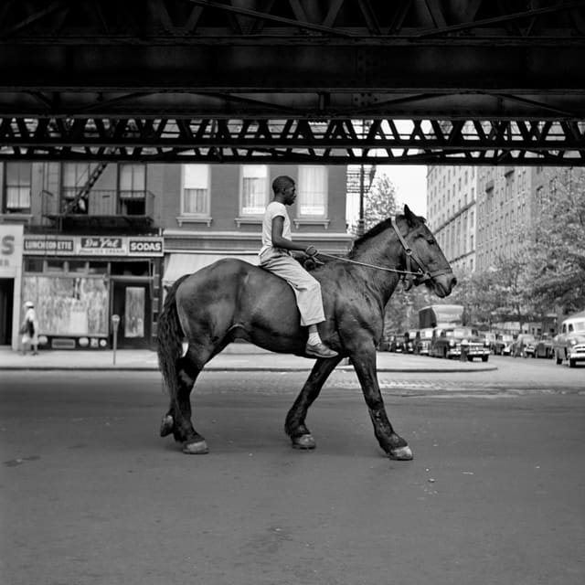 schwarz weiss fotografie. ein schwarzer mann reitet auf einem pferd durch die strassen von New York