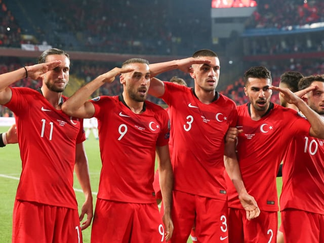 Die türkischen Fussballer greifen mit der rechten Hand an die Stirn.