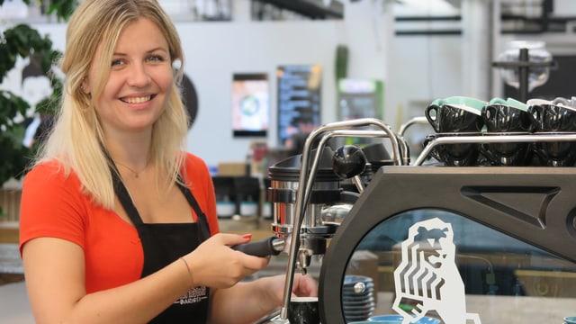 Eine Frau macht Kaffee mit einer professionellen Maschine.