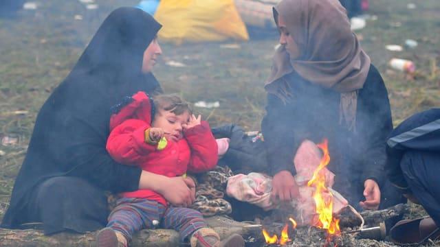 Eine Mutter sitzt mit ihrem Kind an einem Feuer (slowenisch-kroatische Grenze, 23.10.2015)