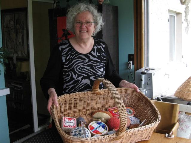 Ältere Frau mit Korb voller gestrickter Lebensmittel.
