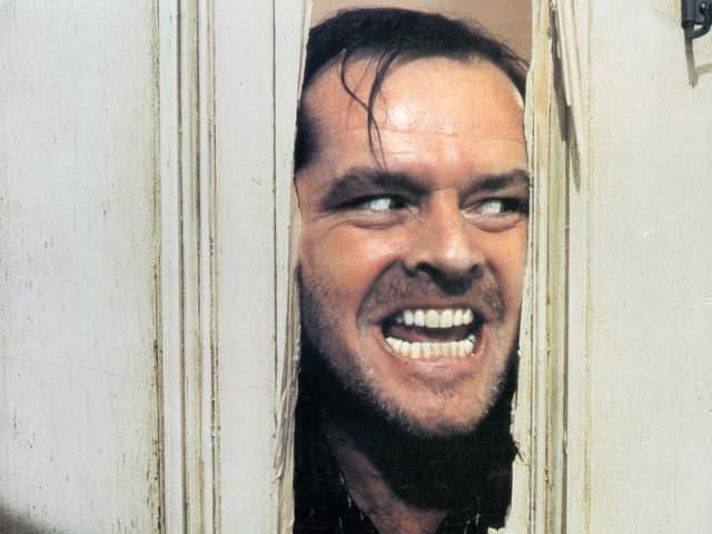 Jack Nicholson steckt als Charakter Jack Torrance den Kopf durch ein Loch in der Tür und grinst diablolisch.