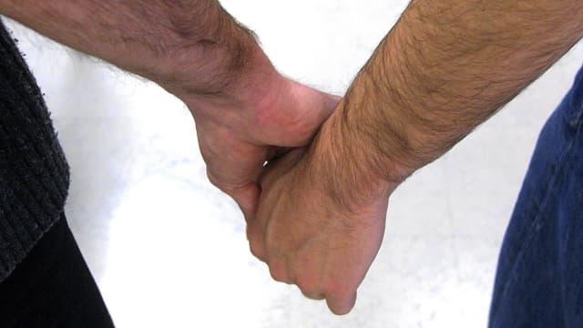 Zwei Männerhände, die sich festhalten.