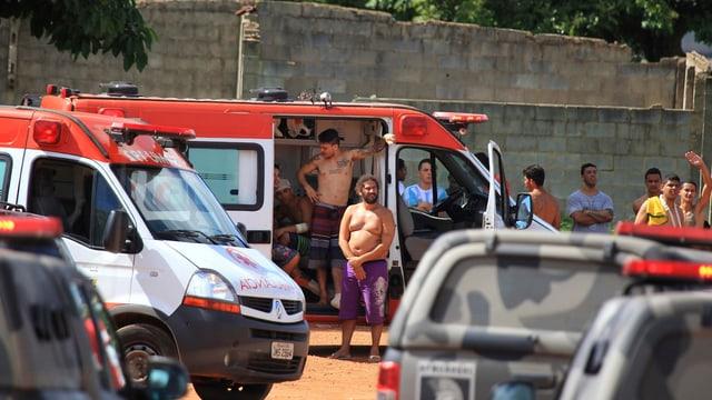 Häftlinge stehen bei einem Ambulanzfahrzeug.