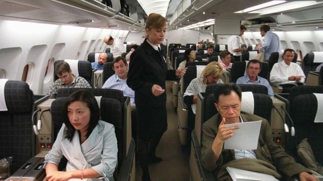 Kabinenpersonal in einem mit Passagieren besetzten Flugzeug.