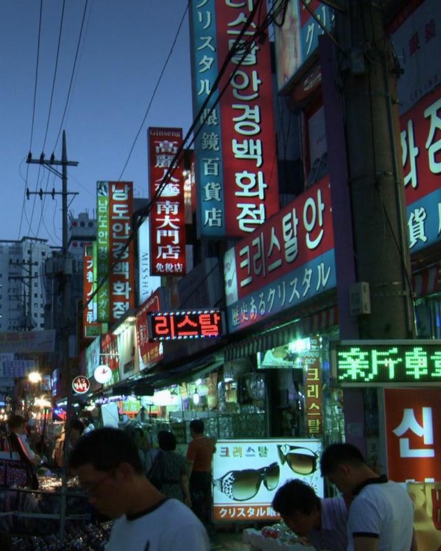 Impression einer beleuchteten südkoreanischen Einkaufsstrasse in der Abenddämmerung.