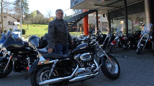 Mann steht hinter seiner schönen Harley - Im Hintergrund Töffladen zu erkennen