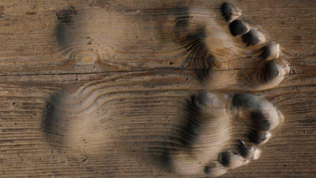 Fussabdrücke in Holz geschnitzt