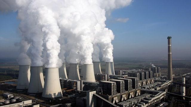 Luftaufnahme eines Kohlekraftwerks in Deutschland mit rauchenden Schloten.