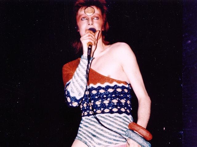 David Bowie in engem, farbigen Anzug, geschminkt.