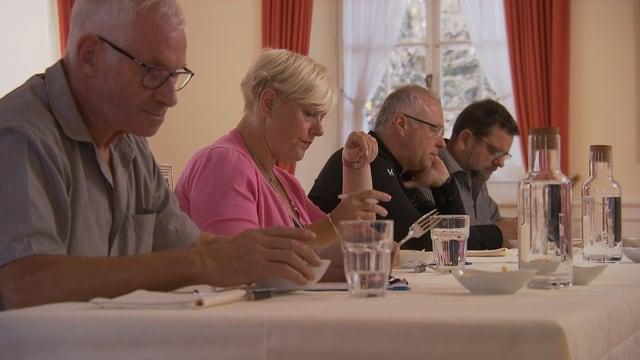 Vier Personen sitzen an einem Tisch und degustieren Spätzli.