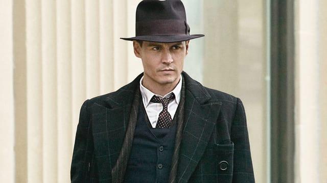 Ein Mann in Anzug und Hut blickt ernst.