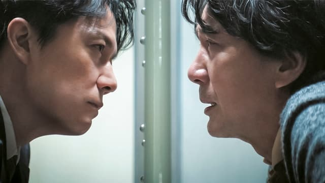 Zwei Männer starren sich an, ihre Gesichter sind durch eine Glasscheibe des Gefängnisses getrennt.
