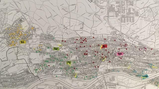 In einer Stadtkarte stecken Stecknadeln in verschiedenen Farben