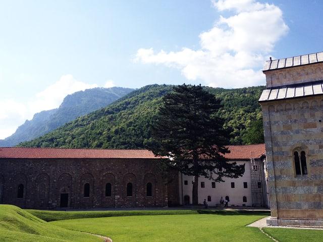 Klostergebäude unter strahlend blauem Himmel vor waldigem Hügel.