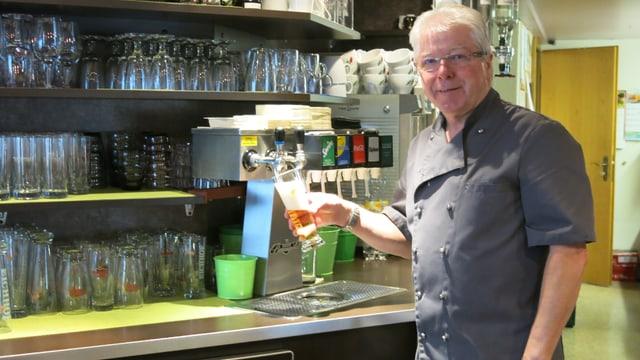Ein Mann steht hinter dem Tresen eines Restaurants und zapft ein Bier.
