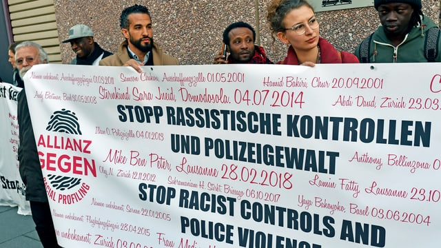 Menschen halten ein Transparent mit Protest gegen rassistische Polizeikontrollen.