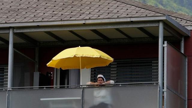 Eine Frau schaut von einem Balkon.