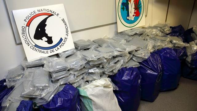 Blaue Plastiksäcke, darauf sind graue Pakete gestapelt, die Kokain enthalten.