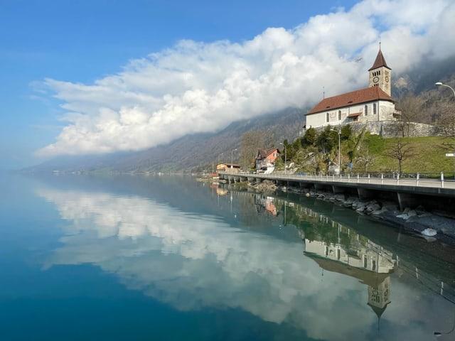 See, in dem sich ein Hang mit Quellwolken spiegelt. Recht eine Kirche am Ufer.