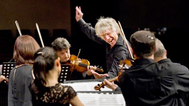 Giovanni Antonini dirigiert mit erhobener rechter Hand und expressivem Gesichtsausdruck.