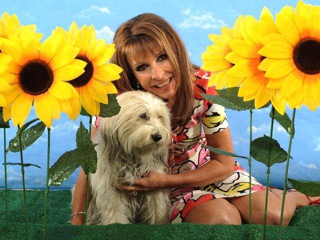 Frau mit Hund umrahmt von künstlichen Sonnenblumen.