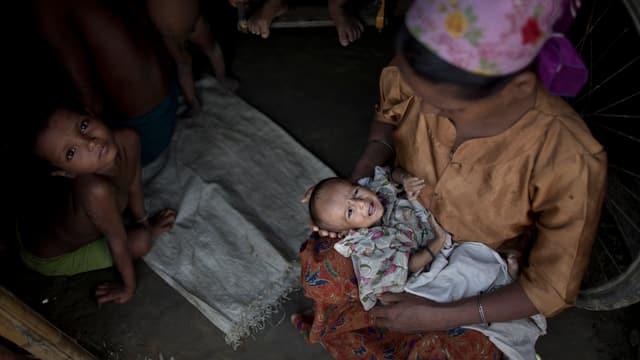 Eine Flüchtlingsfrau hat ihren unterernährten 3 Monate alten Säugling auf dem Arm