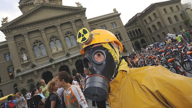 Ein Demonstrant mit gelbem Schutzanzug, Gasmaske und Atom-Symbol auf dem gelben Helm vor dem Bundeshaus in Bern.