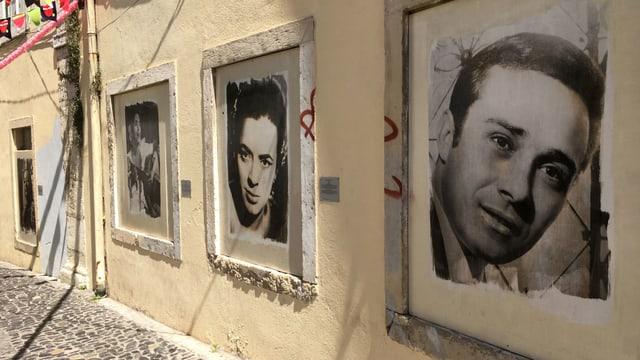 Grossformatige Schwarzweissfotografien hängen an einer Hauswand.