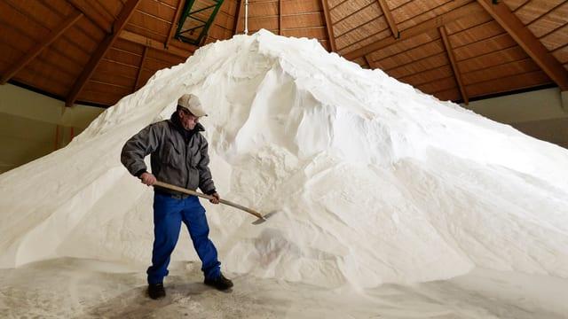 Ein Mann mit Schaufel vor einem Salzberg.