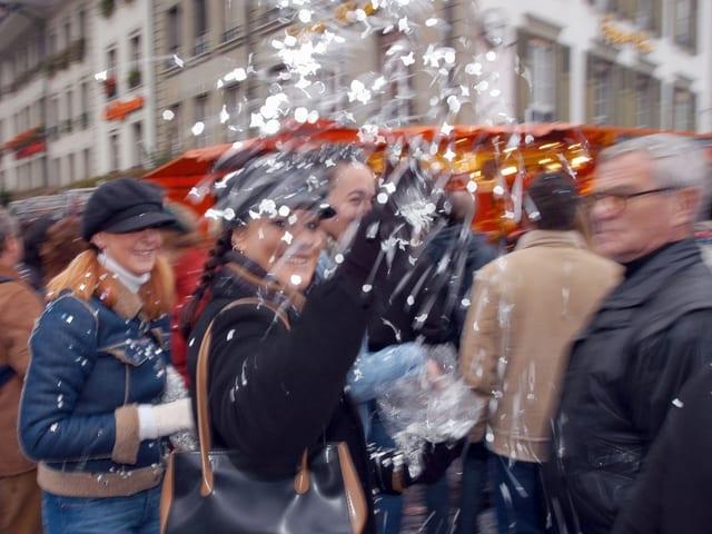 Eine Frau wirft Konfetti in die Kamera.