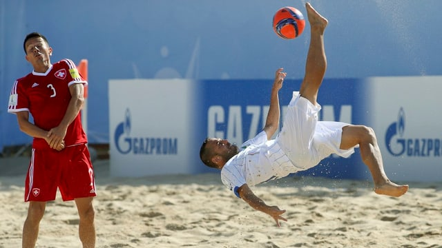 Ein Spieler nimmt im Sand Anlauf zu einem Fallrückzieher.