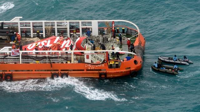 Teile des roten Flugzeughecks auf einem Transportschiff.