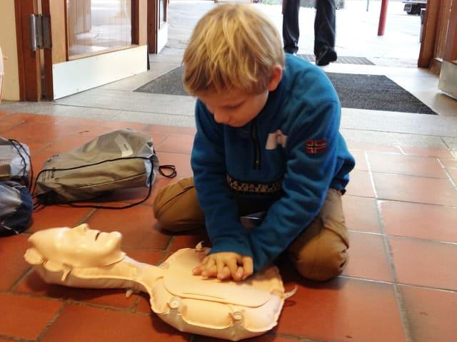 Kleiner Junge übt Herzdruckmassage an einer Puppe.