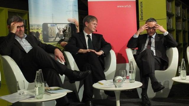 Die drei Kandidaten sitzen auf dem Podium, Nussbaumer und Weber in Denkerpose
