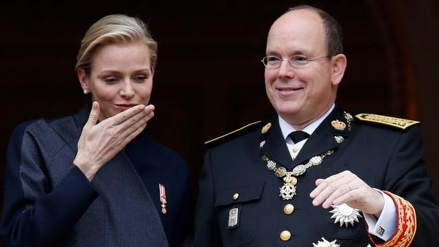 Fürstin Charlène und Fürst Albert lächelnd nebeneinanderstehend.