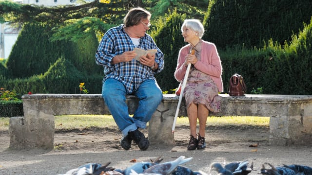 Ein Mann mit einem aufgeschlagenen Buch in der Hand sitzt neben einer älteren Dame mit Gehstock auf einer Parkbank.