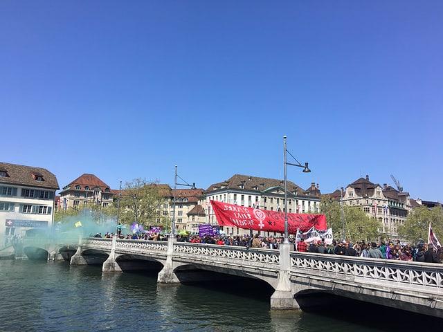 Blick auf die Rudolf-Brun-Brücke in Zürich. Der Umzug zieht darüber, links der Rauch einer Petarde.