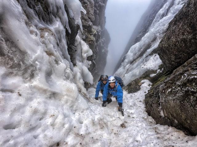 Bergsteiger in einem vereisten Couloir beim Aufstieg, von oben fotografiert.