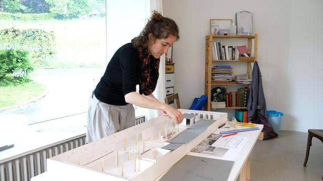Eine Künstlerin im Atelier arbeitet an einem Modell.