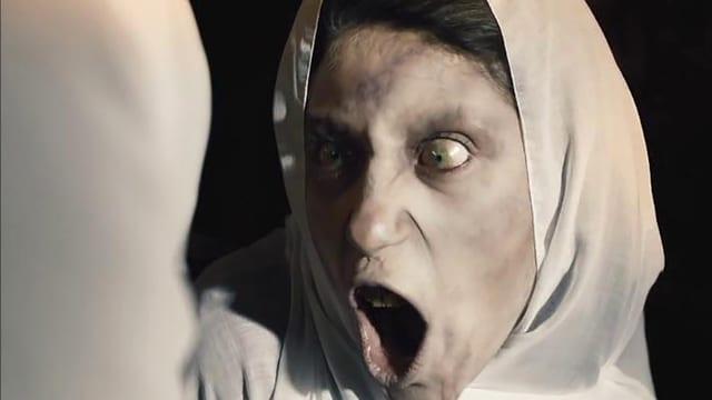 Filmstill aus einem Horrorfilm: Eine Frau mit Kopftoch und weit aufgerissenen Augen.