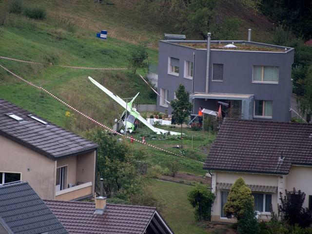 Ein abgestürztes Kleinflugzeug liegt im Garten vor einem Haus